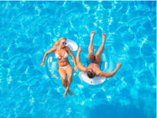 A man and a woman floating in pool rings