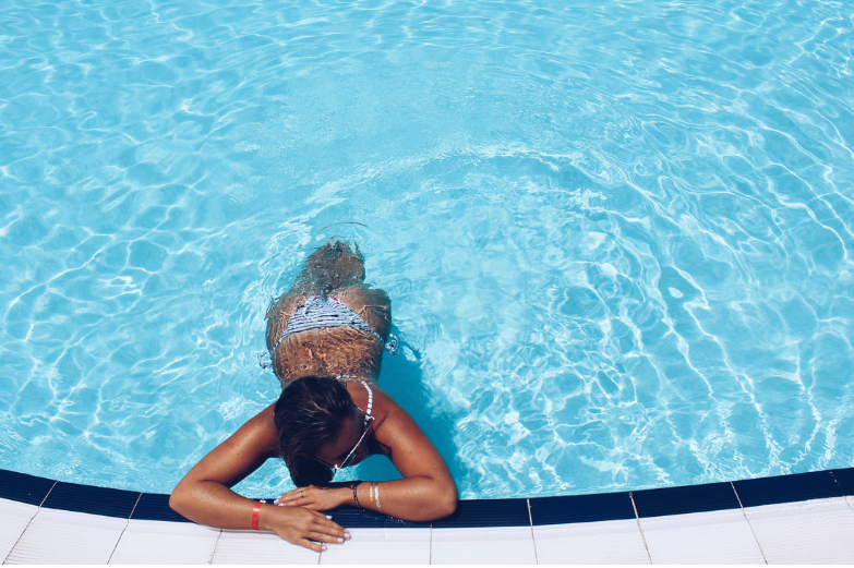 young woman laying in shallow water of a swimming pool