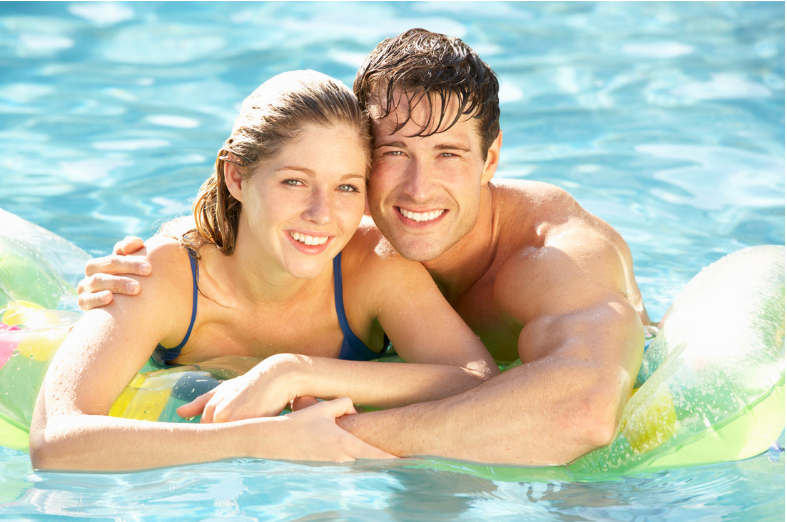 Young man and woman hugging in the pool