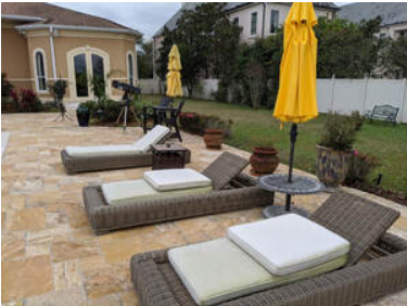 Picture of three lounge chairs next to pool